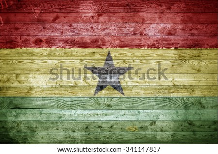 A vignetted background image of the flag of Ghana painted onto wooden boards of a wall or floor. - stock photo