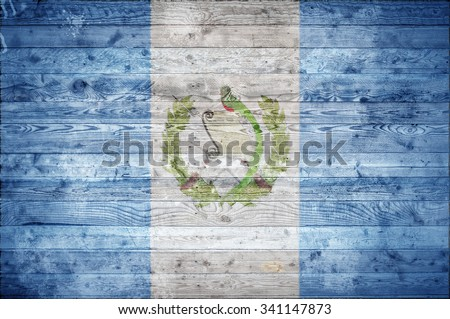A vignetted background image of the flag of Guatemala painted onto wooden boards of a wall or floor. - stock photo