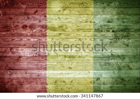 A vignetted background image of the flag of Guinea painted onto wooden boards of a wall or floor. - stock photo