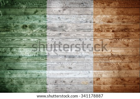 A vignetted background image of the flag of Ireland painted onto wooden boards of a wall or floor. - stock photo
