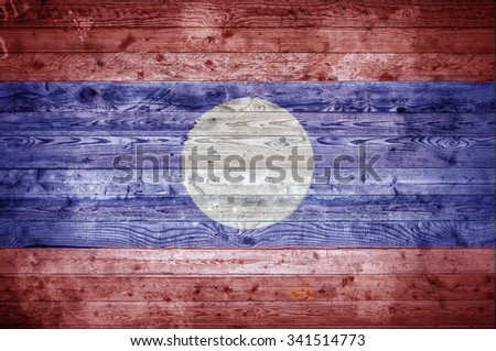 A vignetted background image of the flag of Laos painted onto wooden boards of a wall or floor. - stock photo