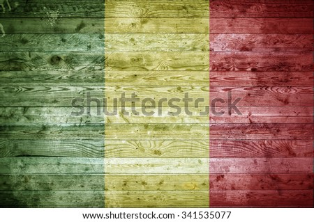 A vignetted background image of the flag of Mali painted onto wooden boards of a wall or floor. - stock photo