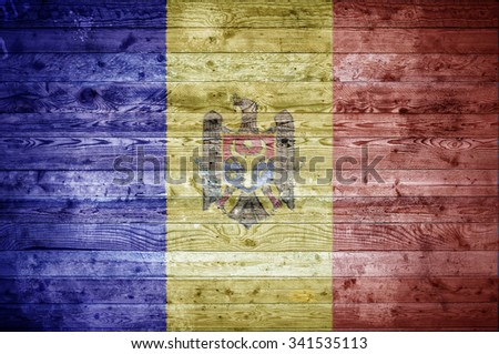 A vignetted background image of the flag of Moldova painted onto wooden boards of a wall or floor. - stock photo