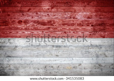 A vignetted background image of the flag of Monaco painted onto wooden boards of a wall or floor. - stock photo