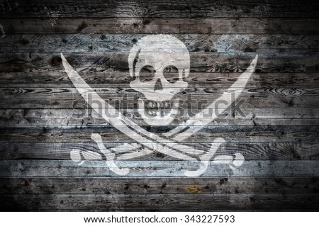 A vignetted background image of the flag of pirates onto wooden boards of a wall or floor. - stock photo
