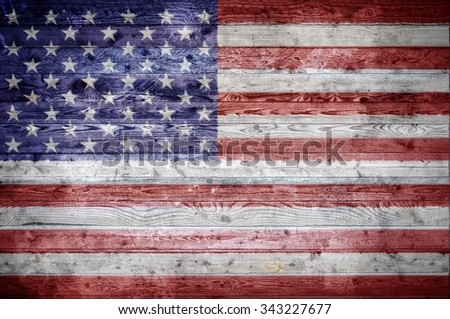 A vignetted background image of the flag of United States onto wooden boards of a wall or floor. - stock photo