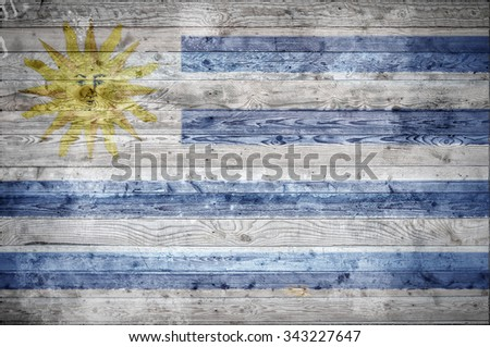 A vignetted background image of the flag of Uruguay onto wooden boards of a wall or floor. - stock photo