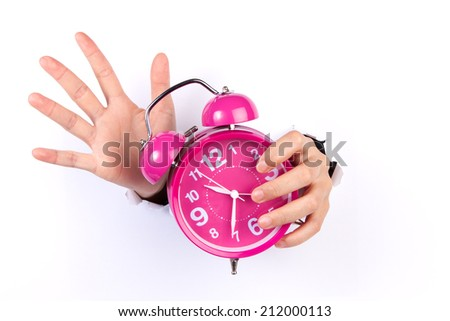 a vintage alarm clock on blue background and a human hand which is about to stop - stock photo