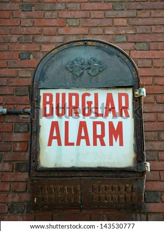 A vintage burglar alarm mounted on a brick wall - stock photo