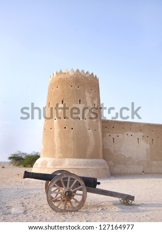 A vintage canon & the southern tower of Zubarah fort, Qatar - stock photo