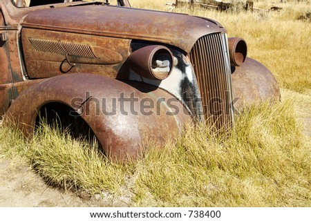 A vintage car left to rust in a ghost town in California. - stock photo