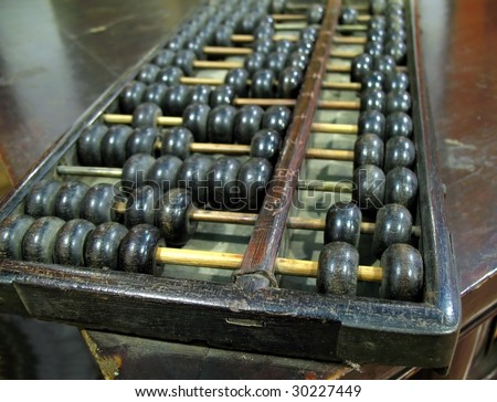 A vintage Chinese abacus or counting frame with two beads in the upper and five in the lower deck. - stock photo