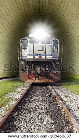 A vintage diesel powered train with a lighted head lamp emerging from a railway tunnel. - stock photo
