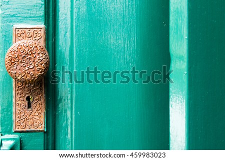 A vintage doorknob and keyhole on the old blue-green wooden door with Mediterranean style - stock photo