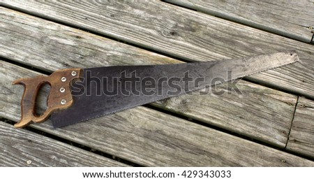 A vintage hand saw on a wood background - stock photo