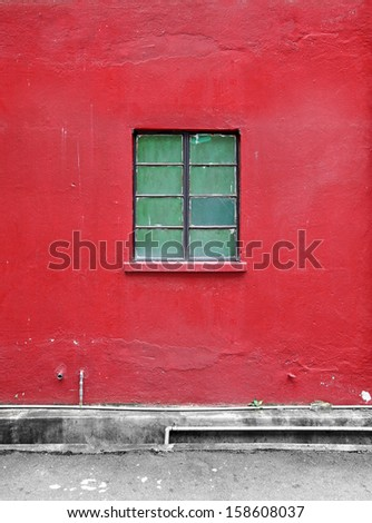 A vintage metal frame window on a grungy red mason wall.  - stock photo