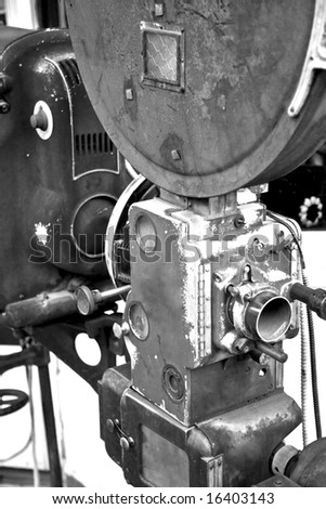 A vintage movie projector from an abandoned movie theater photographed in black and white. - stock photo