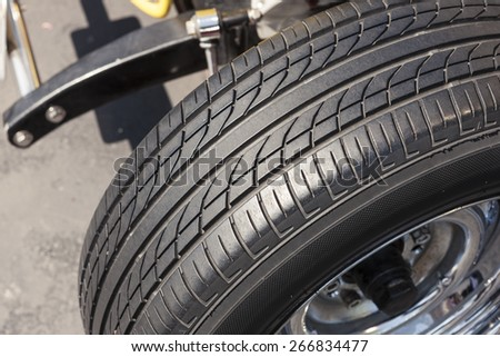 A vintage(old) yellow car rubber tire close up at the daylight. - stock photo