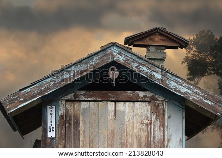 A vintage outhouse with a lock hanging from above. - stock photo