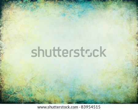 A vintage paper background with textured turquoise, yellow and green grunge patterns with a glowing center. - stock photo