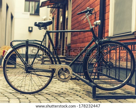 A vintage photo of bicycle parked near a house - stock photo