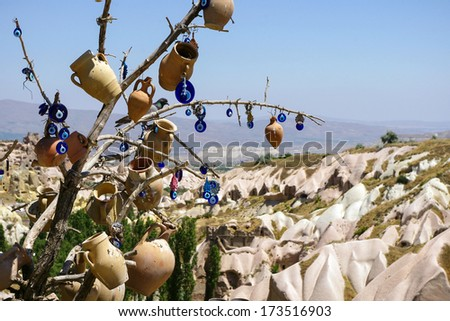 A vintage tree decorated with non-commercial Evil Eyes & pots at Goreme National Park, Cappadocia. Evil Eye is a Turkish traditional ornament dating back to Paganism.  - stock photo