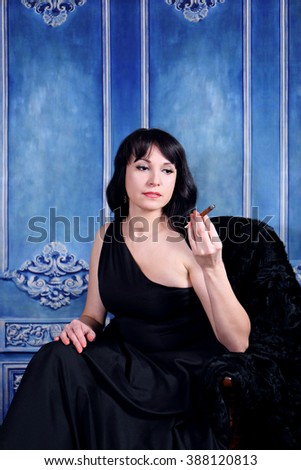 A vintage woman smoking a cigar on blue background - stock photo