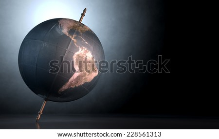 A vintage world globe tilted and standing on a central axis on an isolated spotlit dark background - stock photo