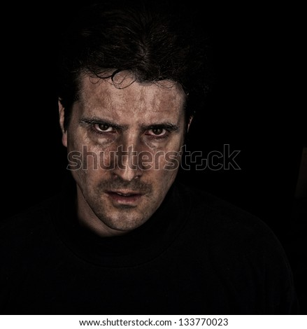 A violent, angry man stares with intense hatred. - stock photo