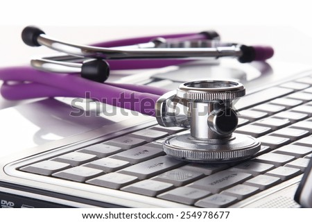 A violet stethoscope on a white laptop computer - stock photo