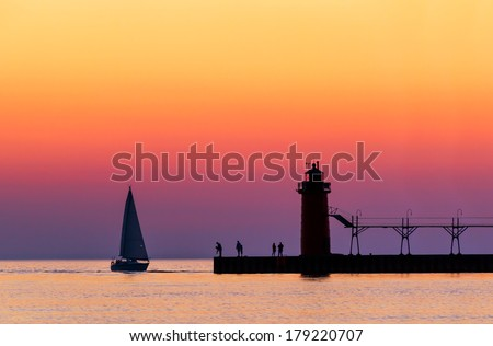 A vividly colorful twilight sky silhouettes a sailboat, people, and the lighthouse at South Haven, Michigan on Lake Michigan. - stock photo