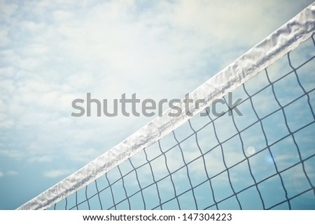 A volleyball next against a blue sky with some clouds. - stock photo