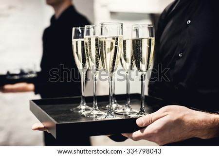 A waiter holding glasses with champagne served on a tablet - stock photo