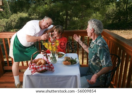 a waiter openly flirts with the wife of one of his customers at an outdoor cafe or bed and breakfast - stock photo