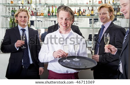 a waiter serving champagne with his customers behind him - stock photo