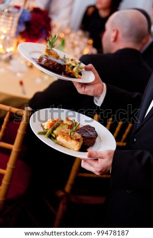 a waiter serving plates of food at a catered wedding - stock photo
