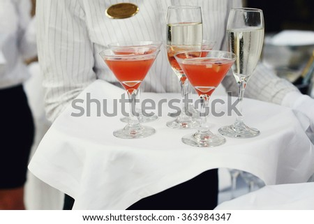 A waiter with a tray of glasses of champagne and a delicious apple punch at the reception. Glasses with alcohol - stock photo