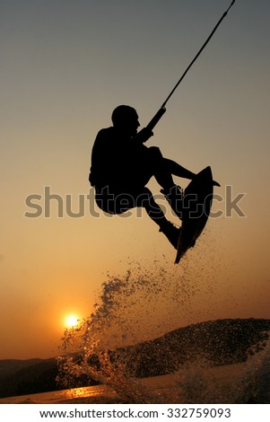 A wakeboarder jumps, shot from in the water during sunset. Hills and sun are behind and splashes of water add to the action. Lots of copy space and great graduated colours. - stock photo