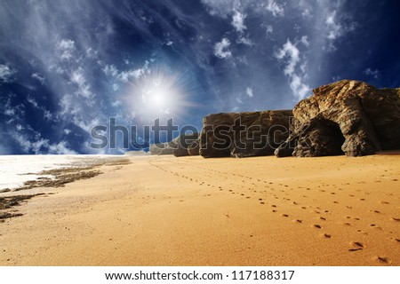 A walk along sand beach and rocks - stock photo