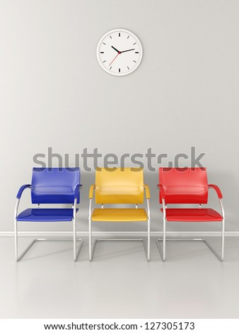 A wall clock and 3 colored chairs in the waiting room - stock photo