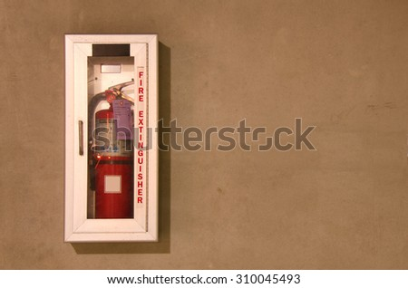 A wall mounted fire extinguisher in an easily accessible glass case. - stock photo