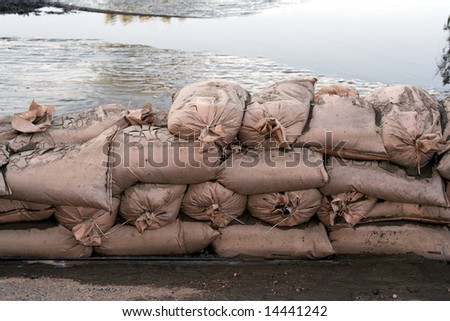 A wall of sandbags holds back floodwaters. - stock photo