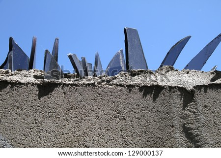 A wall with glass pieces for protection of intruders. - stock photo
