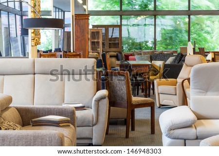 A warehouse with furniture such as sofas, chairs and lamps - stock photo