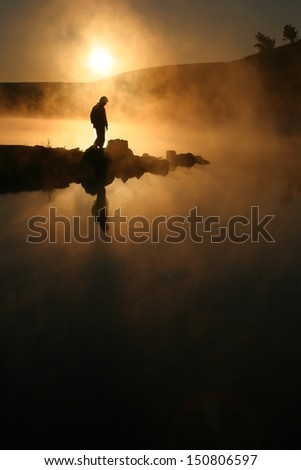A warm, foggy sunrise silhouettes a hiker against a cold early morning mist across a lake.  - stock photo