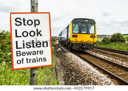 A warning sign cautions pedestrians at a crossing on a railway line with two train tracks as a train passes - stock photo
