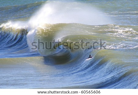 A warped Ocean wave with lone surfer watching - stock photo