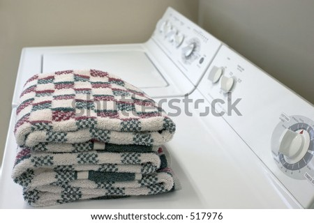 A washer and dryer with folded towels - stock photo