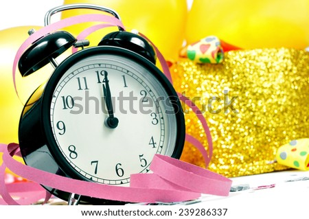 a watch at twelve, balloons, golden top hat, party horns, streamers and confetti for the new years party - stock photo
