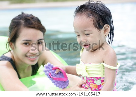 A watchful lady and a little girl in the swimming pool. - stock photo